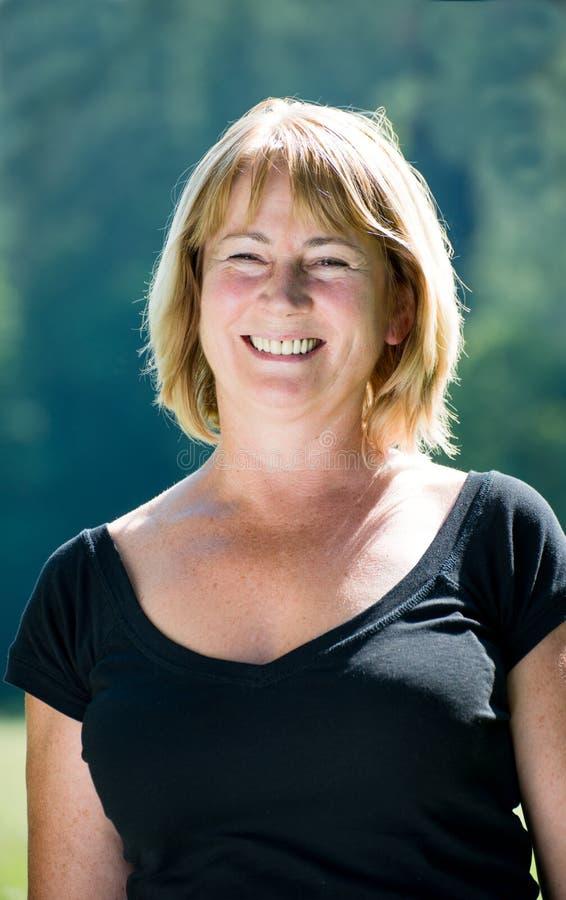 Het glimlachen rijp vrouwen openluchtportret stock afbeelding