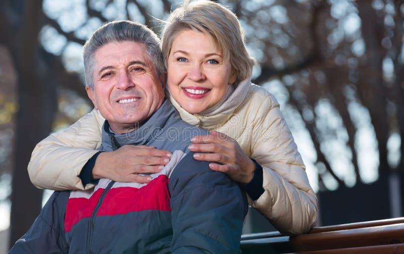 Het glimlachen rijpe echtpaarzitting op parkbank stock foto