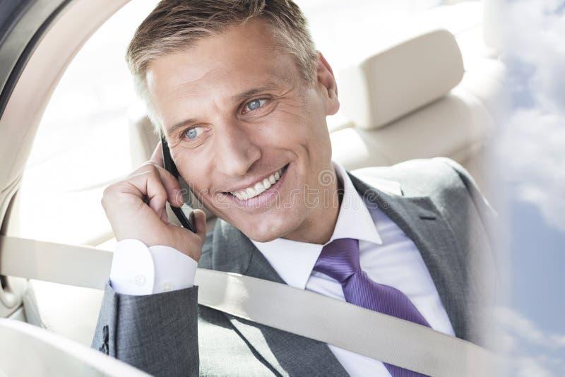 Het glimlachen het rijpe uitvoerende spreken op smartphone in auto royalty-vrije stock afbeelding