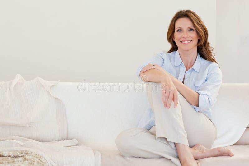 Het glimlachen rijpe vrouwenzitting op bank royalty-vrije stock afbeeldingen