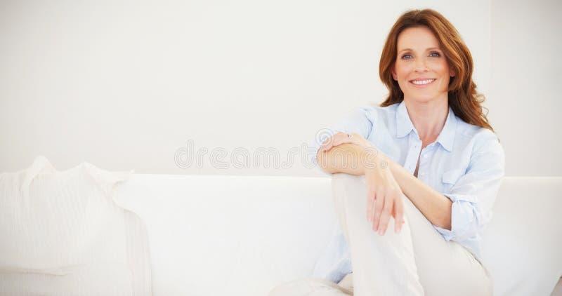 Het glimlachen rijpe vrouwenzitting op bank royalty-vrije stock afbeelding
