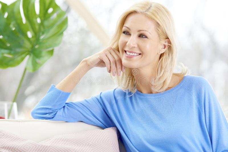 Het glimlachen rijpe vrouwenzitting op bank thuis stock foto
