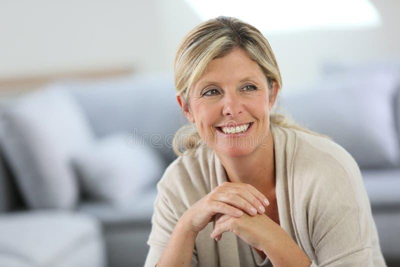 Het glimlachen rijpe vrouwenzitting thuis royalty-vrije stock afbeelding