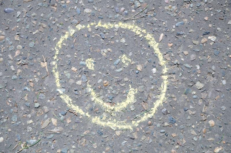 Het glimlachen schilderde gezicht met kleurrijk die krijt op asfalt, smileyteken openlucht door kinderen wordt geschetst terwijl  royalty-vrije stock fotografie