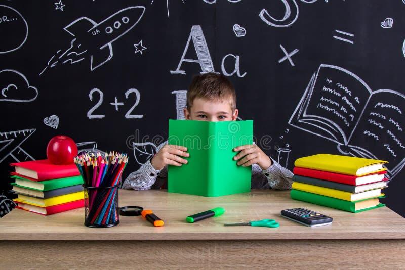 Het glimlachen schooljongenzitting bij het bureau met een boek vóór het gezicht, die na het boek verbergen, met school wordt omri royalty-vrije stock fotografie