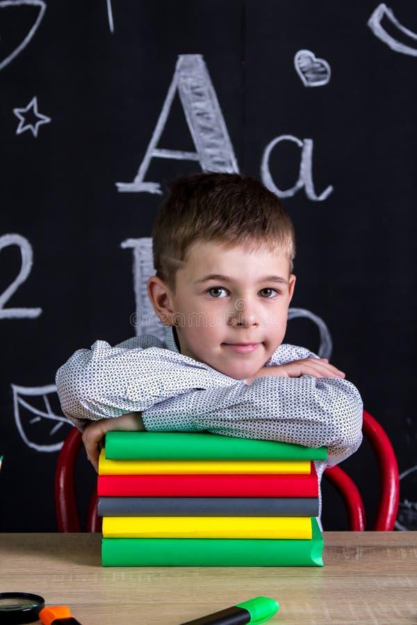 Het glimlachen schooljongenzitting bij het bureau met een stapel van boeken onder de kin, met schoollevering die wordt omringd bo royalty-vrije stock foto