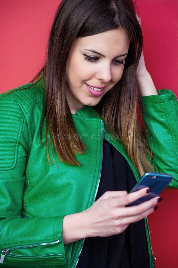 Het glimlachen smartphone openluchtportret van het meisjesgebruik royalty-vrije stock afbeeldingen