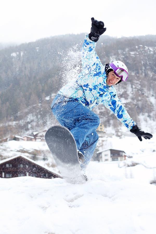 Het glimlachen snowboarder springt op snowboard op berg stock afbeeldingen