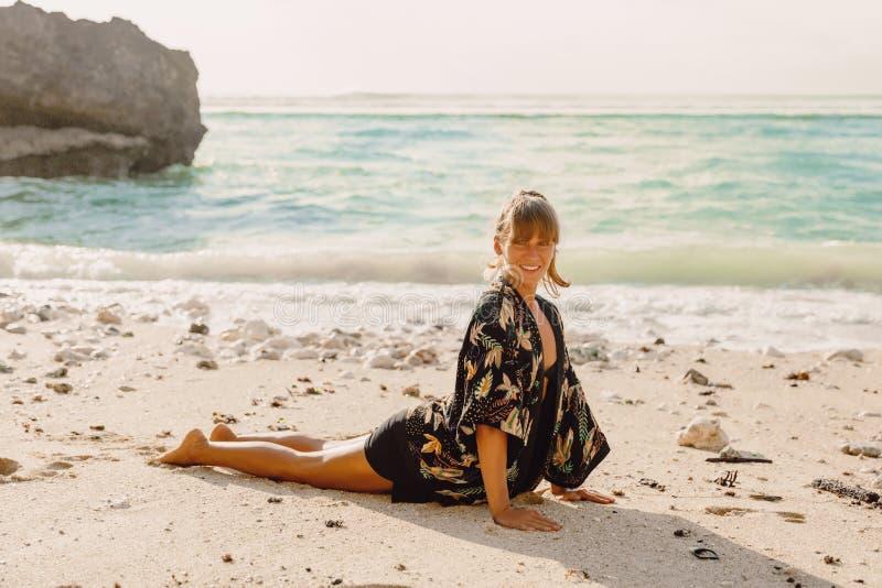 Het glimlachen sportieve vrouw het praktizeren yoga bij avondstrand stock foto's