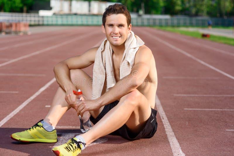 Het glimlachen sportmanzitting en het hebben van rust stock foto's