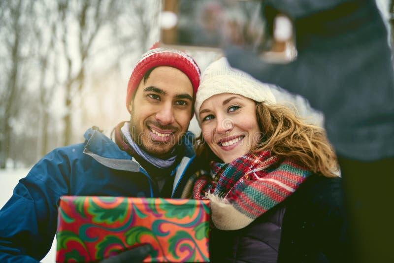 Het glimlachen stelt diverse Kerstmis van de paarholding en holding een mobiele telefoon voor om een selfie te nemen terwijl het  stock afbeeldingen