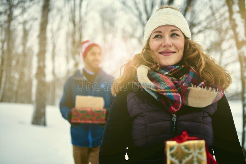 Het glimlachen stelt diverse Kerstmis van de paarholding terwijl het lopen door een de winterbos voor stock afbeeldingen
