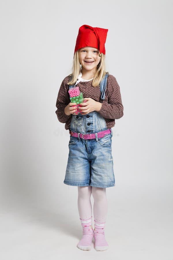 Het glimlachen stelt gelukkige Kerstmis van de meisjesholding voor stock foto's