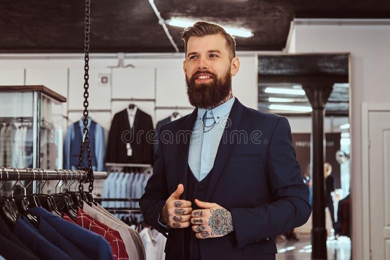 Het glimlachen tattoed mannetje met modieuze baard en het haar kleedde zich in elegant kostuum die zich in menswear opslag bevind royalty-vrije stock fotografie