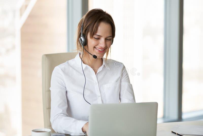 Het glimlachen telemarketer dragend hoofdtelefoon het raadplegen klant het maken stock foto's