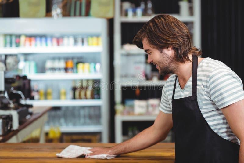 Het glimlachen teller van de kelners de schoonmakende koffie stock afbeeldingen