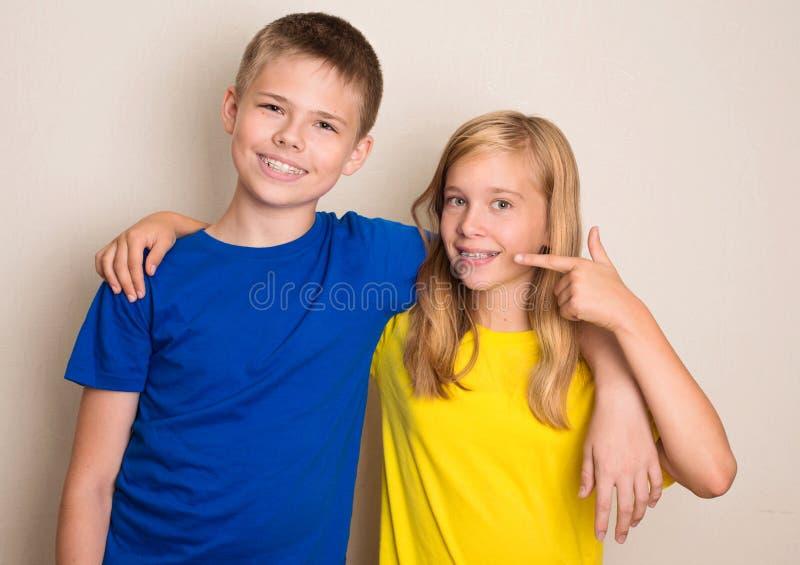 Het glimlachen tienerjaren met verschillende soorten die tandsteun duim op gebaar tonen Gezondheidszorggezondheid en mensenconcep royalty-vrije stock foto's
