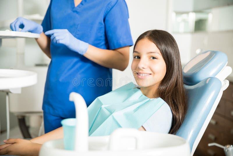 Het glimlachen Tienerzitting op Stoel door Tandarts Standing In Clinic stock afbeeldingen