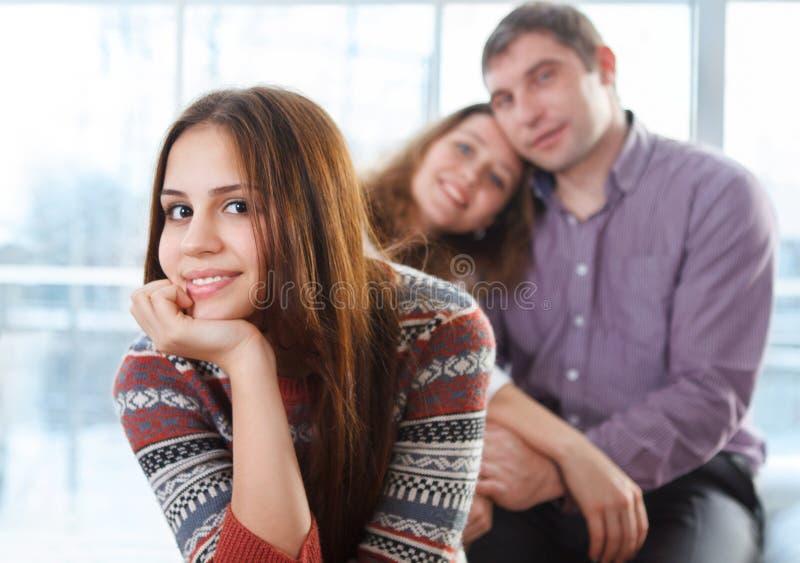 Het glimlachen tienerzitting voor haar ouders royalty-vrije stock afbeelding