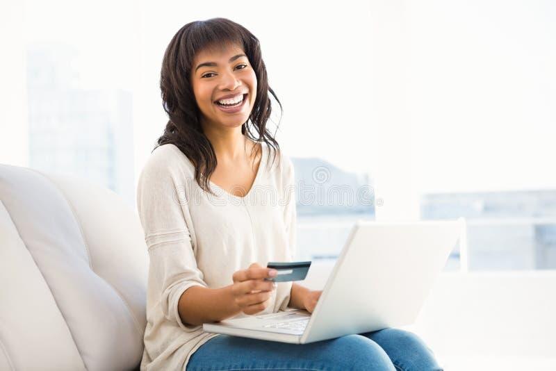 Het glimlachen toevallige vrouw het kopen dingen met haar laptop stock foto
