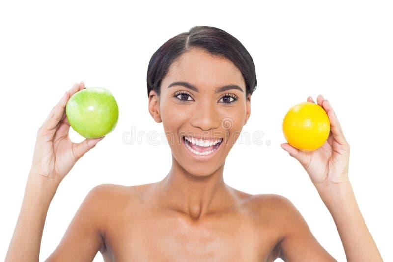 Het glimlachen van aantrekkelijke modelholdingsvruchten in beide handen stock afbeelding