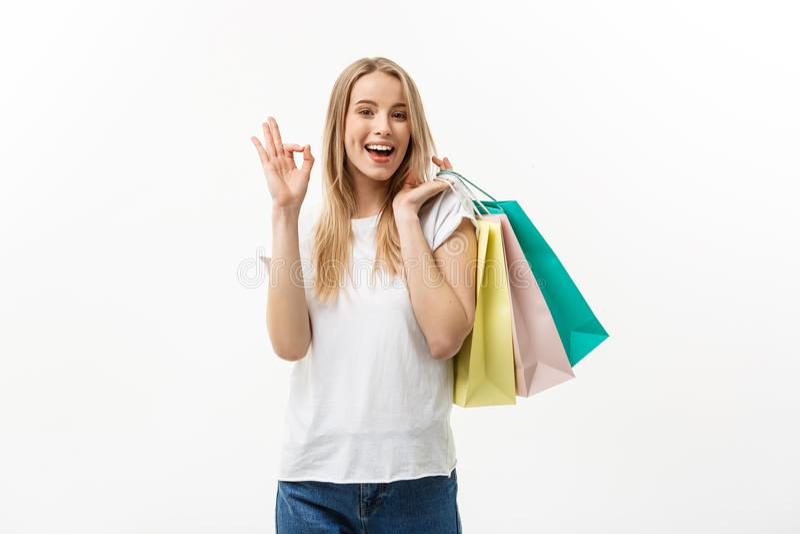 Het glimlachen van aantrekkelijke vrouwenholding het winkelen zakken die o.k. teken op witte achtergrond met copyspace doen stock foto