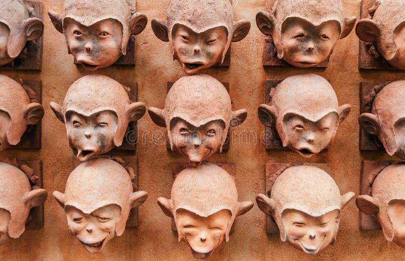 Het glimlachen van Aap hoofd oude ceramische beeldhouwwerken op muur in Samui-isla stock afbeeldingen