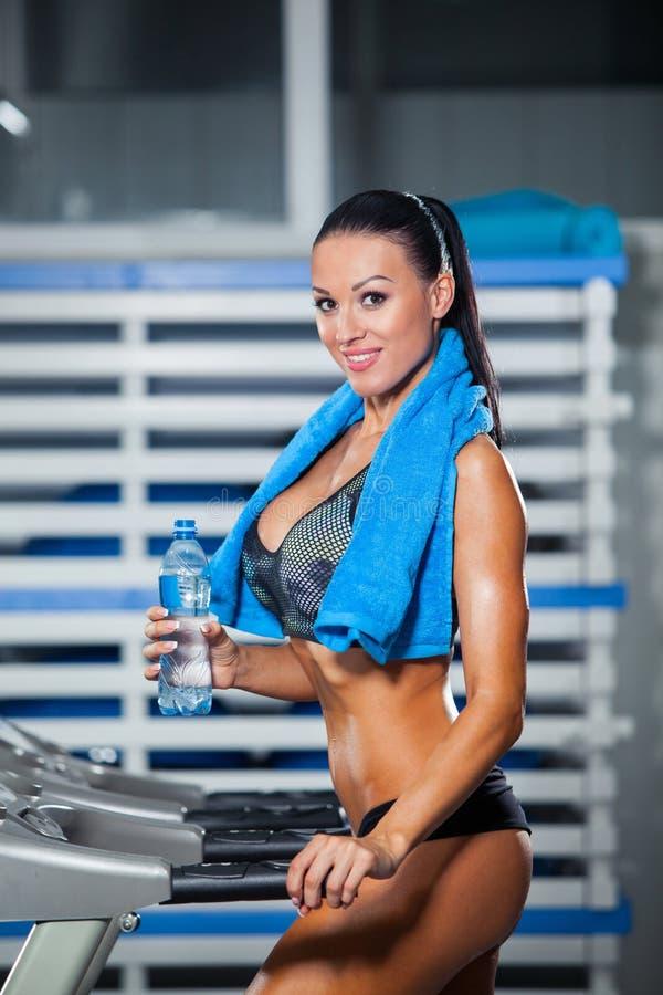Het glimlachen van atletisch vrouwen drinkwater op a stock foto's