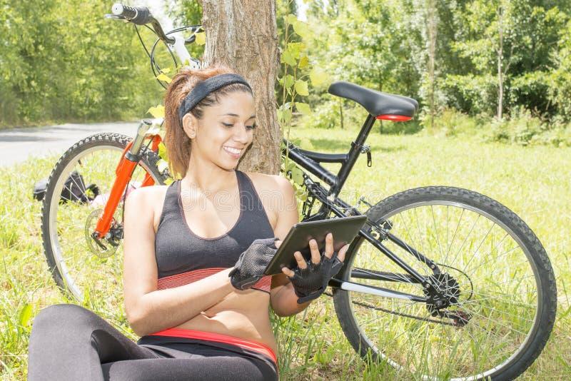 Het glimlachen van atletische vrouwenlaptop tabletcomputer na het uitoefenen, stock foto