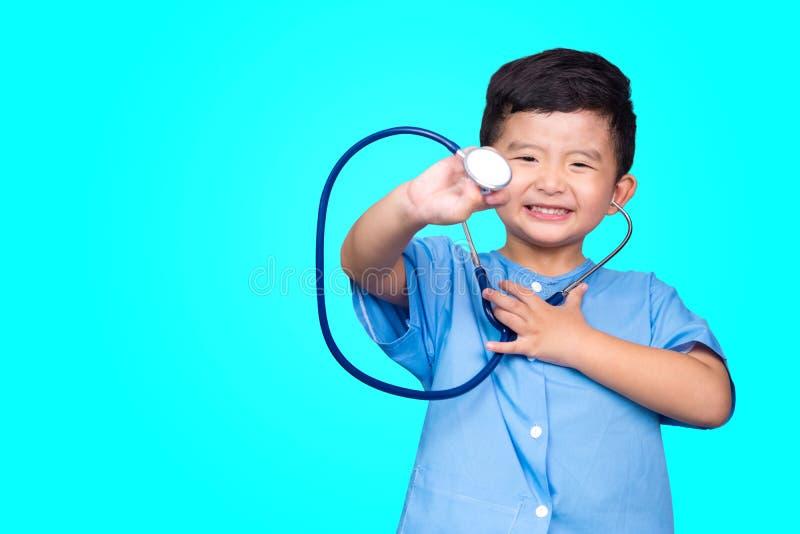 Het glimlachen van Aziatisch jong geitje in blauwe medische eenvormige holdingsstethoscoop die camera op blauwgroene achtergrond  royalty-vrije stock fotografie