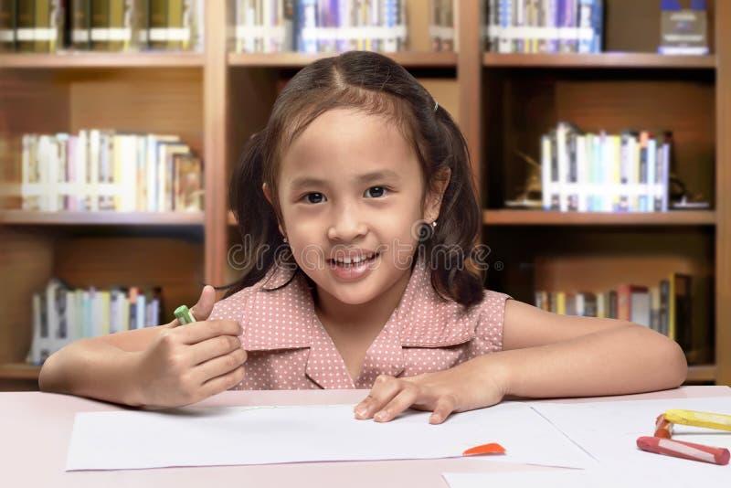 Het glimlachen van Aziatische leuke meisjetekening met kleurpotlood stock foto's