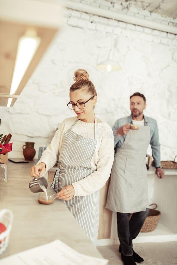 Het glimlachen van barista gietende melk in een koffiekop royalty-vrije stock foto's