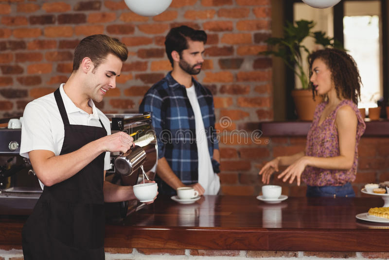 Het glimlachen van barista gietende melk in kop voor klanten royalty-vrije stock foto