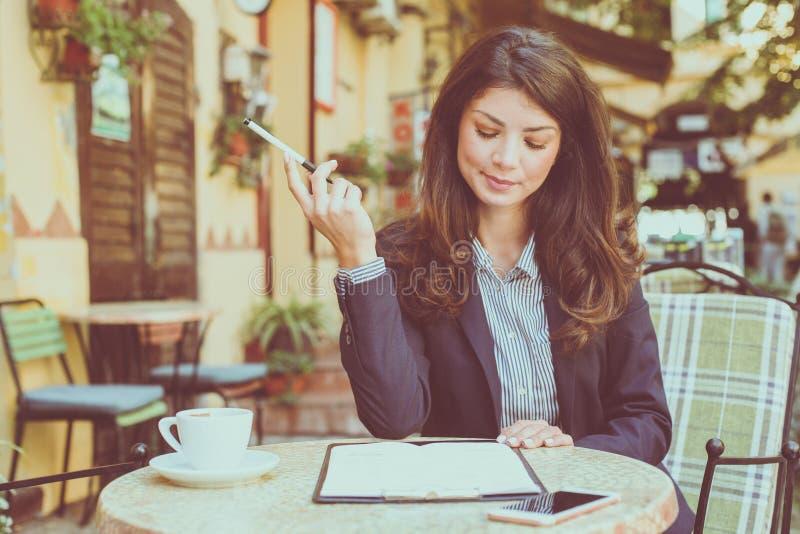Het glimlachen van bedrijfsvrouwenbriefpapieren bij koffie royalty-vrije stock foto