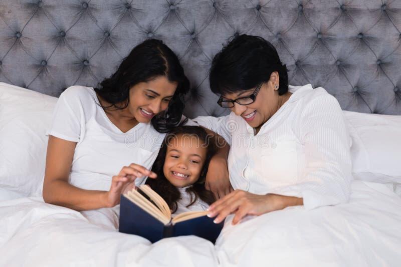 Het glimlachen van boek het van meerdere generaties van de familielezing terwijl het rusten op bed stock fotografie