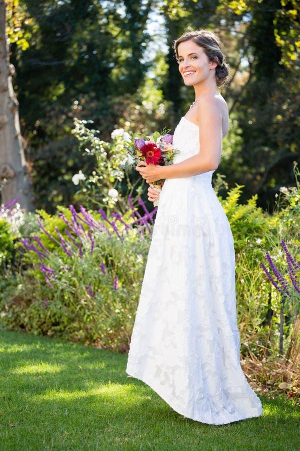 Het glimlachen van het boeket van de bruidholding terwijl status op grasrijk gebied royalty-vrije stock afbeelding