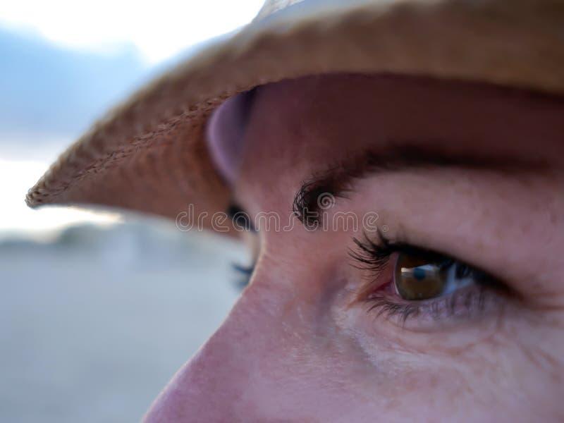 Het glimlachen van bruine ogen van een jonge vrouw in een hoed, close-up stock afbeeldingen