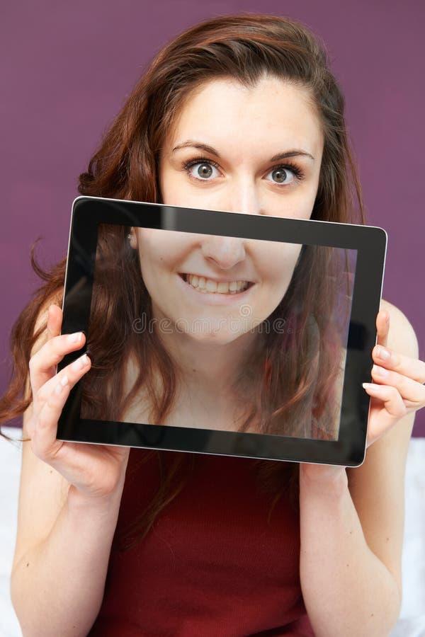 Het glimlachen van de Digitale Tablet van de Tienerholding in Front Of Face stock foto