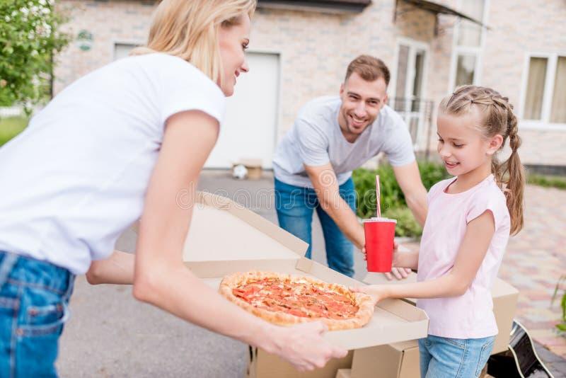 het glimlachen van de doos van de moederholding met pizza en dochter die plak van pizza nemen terwijl vader het uitpakken royalty-vrije stock afbeelding