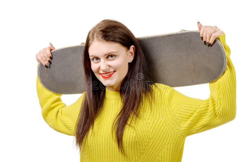 Het glimlachen van de holdingsskateboard van het schaatsermeisje op wit royalty-vrije stock afbeeldingen