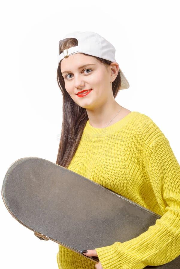 Het glimlachen van de holdingsskateboard van het schaatsermeisje op wit stock afbeeldingen