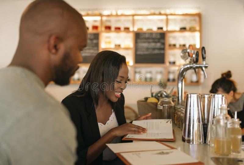 Het glimlachen van de jonge Afrikaanse Amerikaanse menu's van de paarlezing in een bar stock foto's