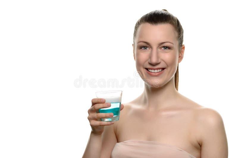Het glimlachen van de Jonge Mondspoeling van de Vrouwenholding in een glas royalty-vrije stock afbeeldingen