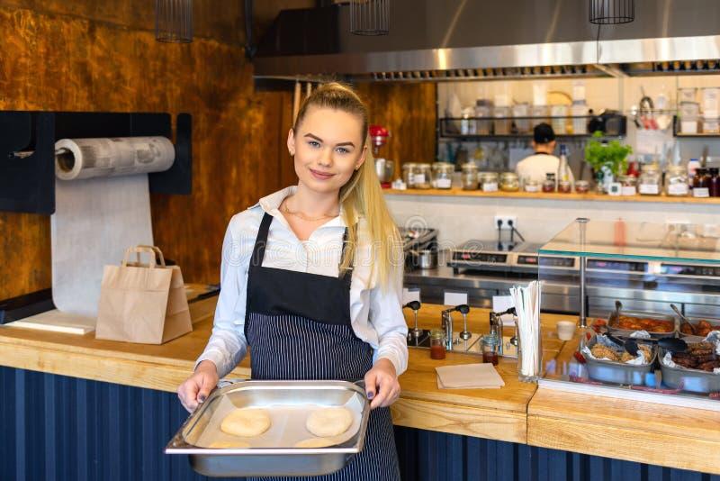 Het glimlachen van van de kleine het dienblad bedrijfseigenaarholding van brooddeeg, Gelukkige bakker met schort die in commercië royalty-vrije stock fotografie