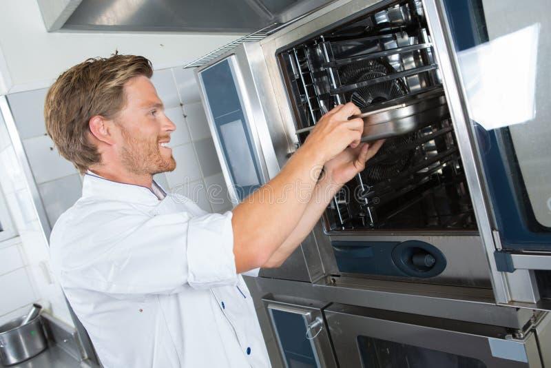Het glimlachen van de knappe mannelijke schotel van de kokholding in restaurantkeuken stock foto
