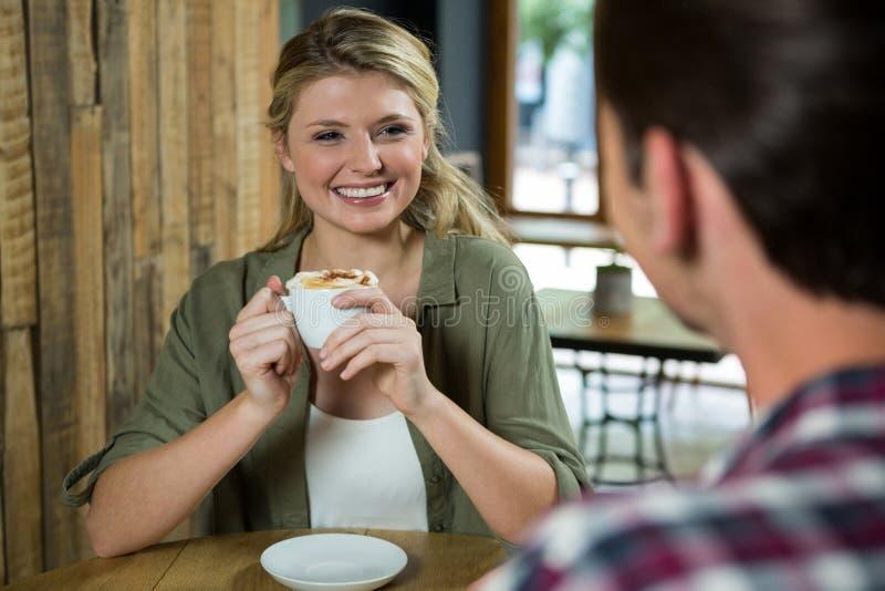 Het glimlachen van de koffiekop van de vrouwenholding terwijl het bekijken de mens in koffie stock afbeeldingen