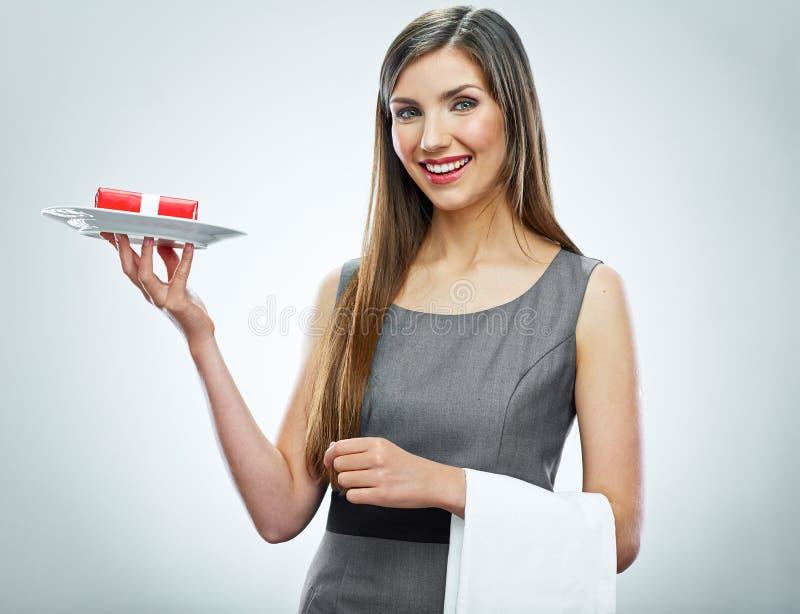 Het glimlachen van de rode gift van de bedrijfsvrouwengreep op een plaat stock foto's