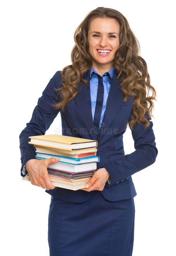 Het glimlachen van de stapel van de bedrijfsvrouwenholding boeken stock foto's
