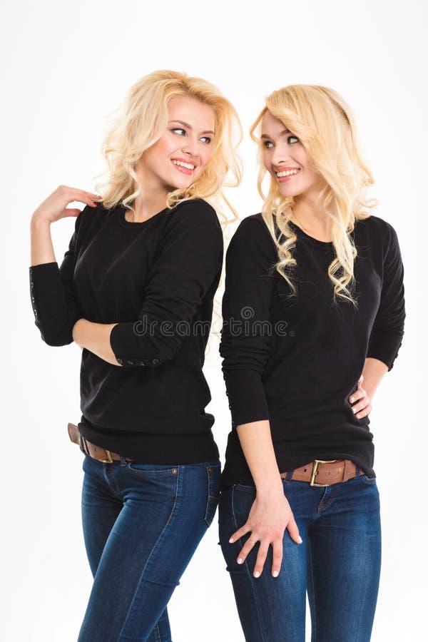 Het glimlachen van de tweelingen die van blondezusters elkaar bekijken royalty-vrije stock foto's