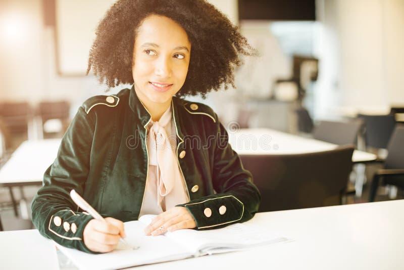 Het glimlachen van de vrij Latijnse zitting van het studentenmeisje in klassenruimte royalty-vrije stock fotografie